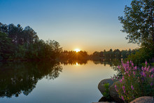 Sunset On A Lake With Blue Water And Sky, In The Foreground Lavender And Round Stones