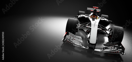 Modern race car in spotlight on black background.