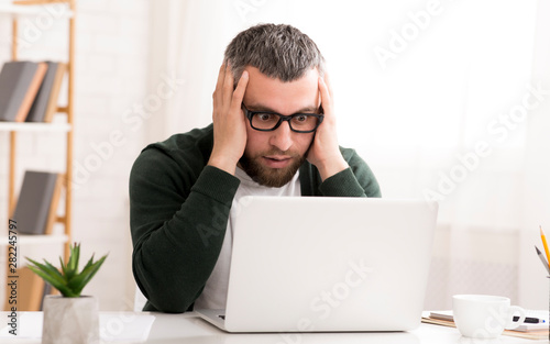 Photo  Shocked caucasian man is sitting in front of laptop