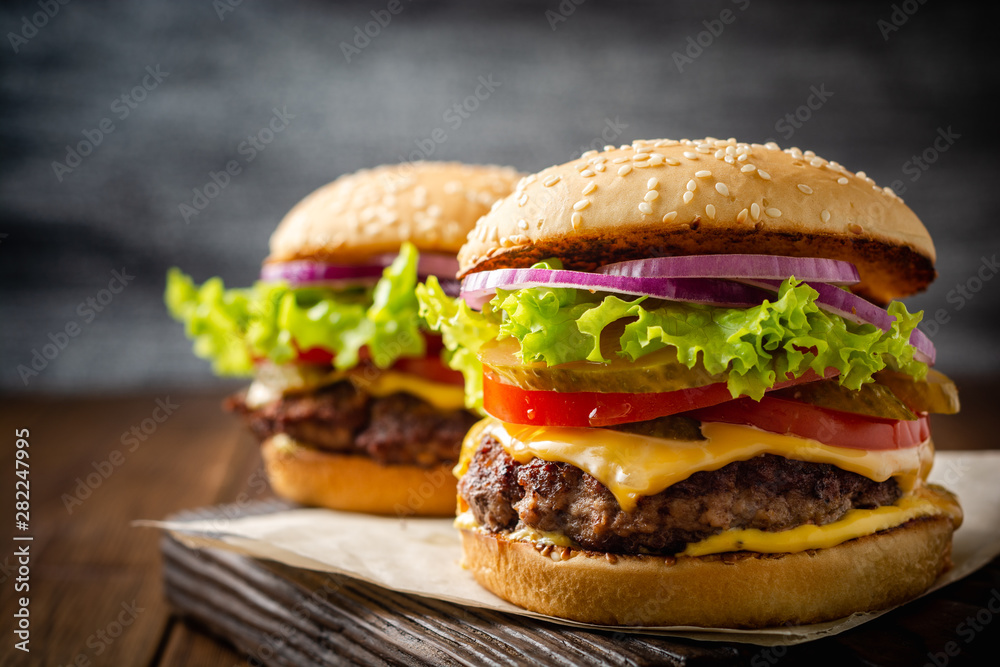 Fototapety, obrazy: Two homemade tasty burgers on wood table. Selective focus.