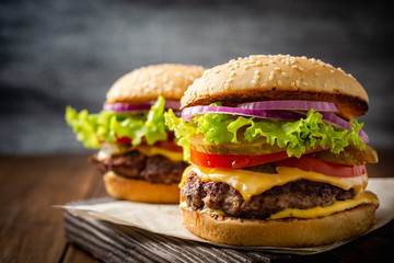 Two homemade tasty burgers on wood table. Selective focus.