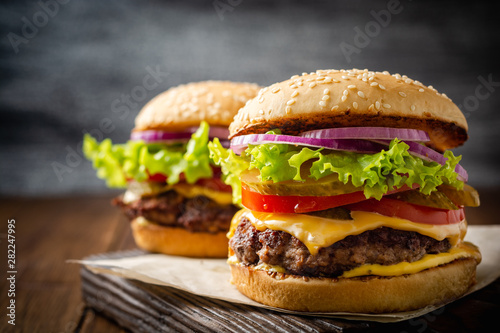 Two homemade tasty burgers on wood table. Selective focus. Wallpaper Mural