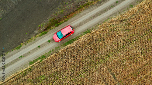 Fototapeta Top view of a field with wheat and a red car moving on the rural road. Aerial view from drone obraz