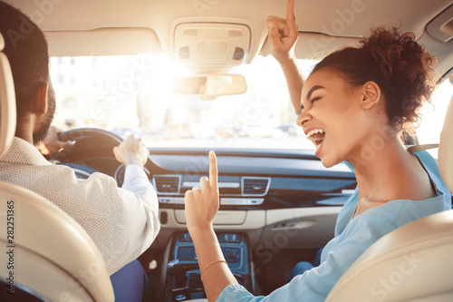 Fotografía Happy afro couple driving in car and singing song