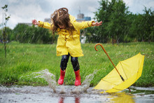 Happy Child Girl With An Umbrella And Rubber Boots In Puddle  Jump