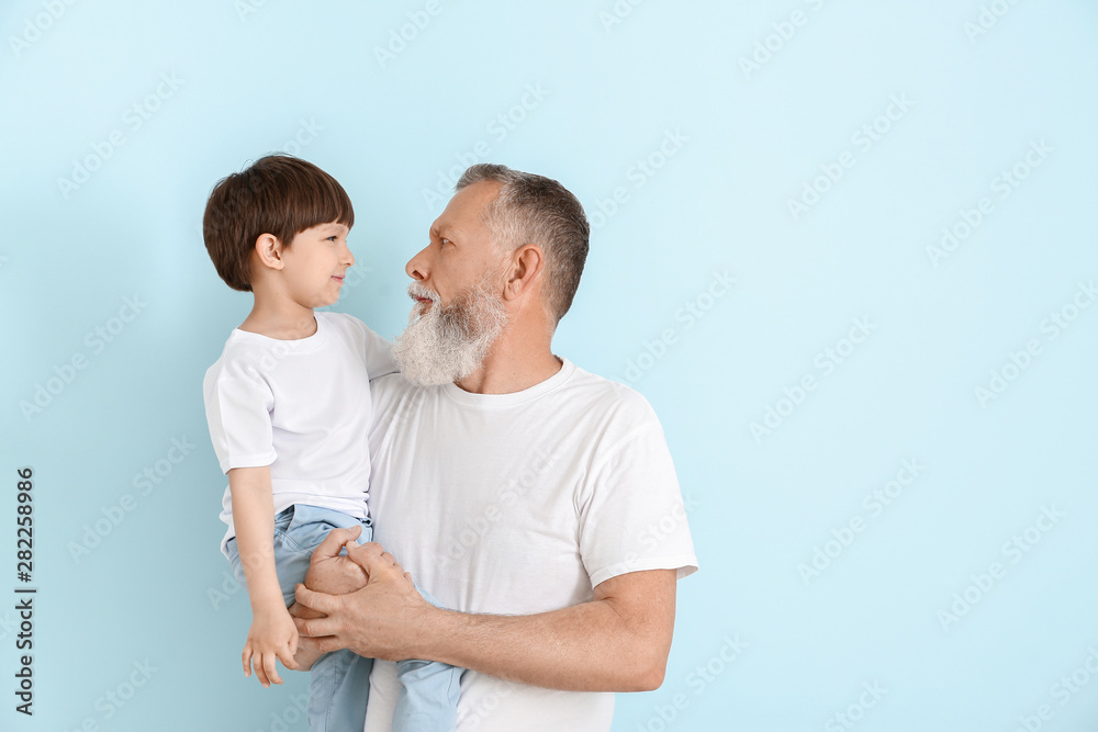 Fototapety, obrazy: Cute little boy with grandfather on light background
