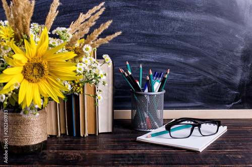 Books, glasses, markers and a bouquet of flowers in a vase on white board background. Concept for teachers day and first September. Copy space. - 282260933