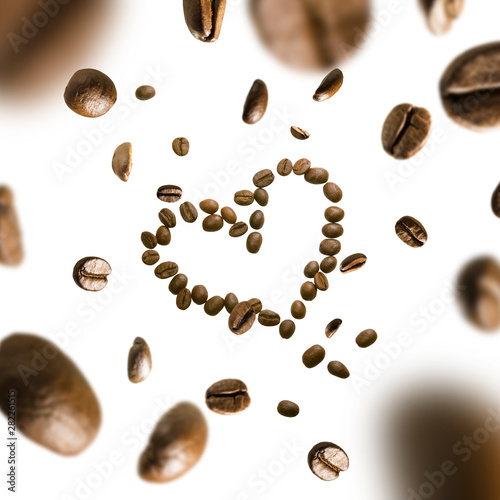 Obraz na plátně  Coffee beans in the shape of a heart in flight on a white background