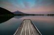 Wooden pier on Tanukiko Lake in front of Mount fuji at sunset