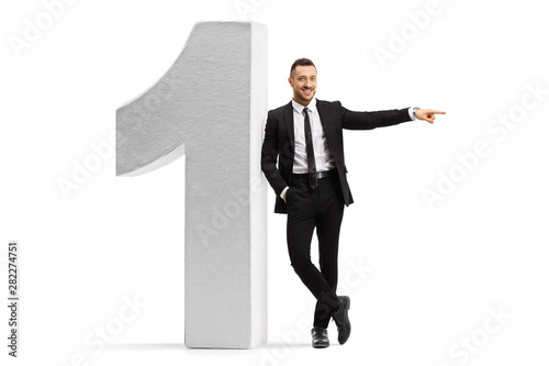 Cuadros en Lienzo Young businessman leaning on a large number one and pointing to the side