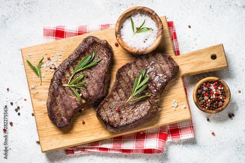 Fotografie, Obraz  Grilled beef steak on wooden cutting board.