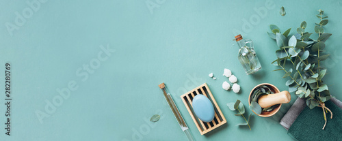 Soap, eucalyptus, towels, massage brush, salt, aroma oil and other spa objects on green background. Top view. Skin care, body treatment concept. Banner.