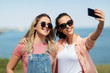 leisure and friendship concept - happy smiling teenage girls or best friends in sunglasses hugging and taking selfie by smartphone at seaside in summer