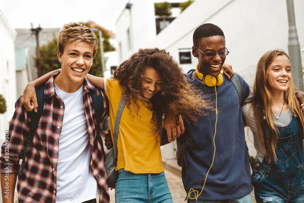 Fototapeta Cheerful teenage friends enjoying outdoors