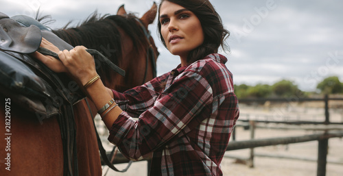 Photo Cowgirl saddling a brown horse
