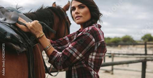 Fototapeta Cowgirl saddling a brown horse obraz