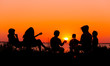 canvas print picture - Silhouette of people sitting on the beach with campfire at sunse