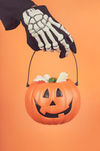 Happy Halloween.Child's Hand In A Skeleton Glove With Halloween Pumpkin