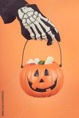 Foto auf Leinwand Logo Happy Halloween.Child's hand in a skeleton glove with halloween pumpkin
