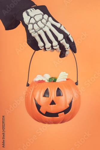 Leinwanddruck Bild - esthermm : Happy Halloween.Child's hand in a skeleton glove with halloween pumpkin