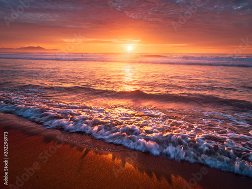 Foto  beautiful red sunset on beach with a wave on the shore
