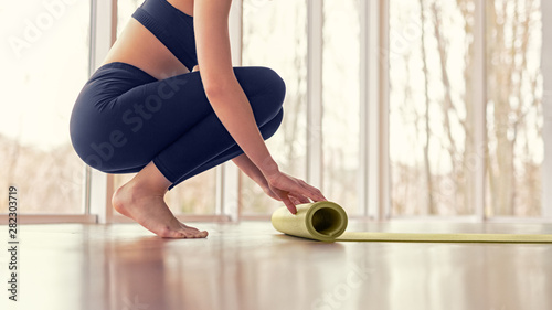 Staande foto School de yoga Crop female unrolling mat before yoga lesson
