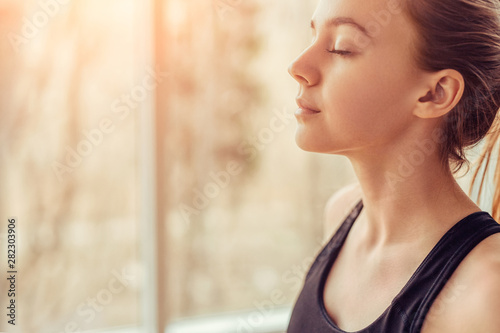 Fototapeta Young woman doing breathing exercise