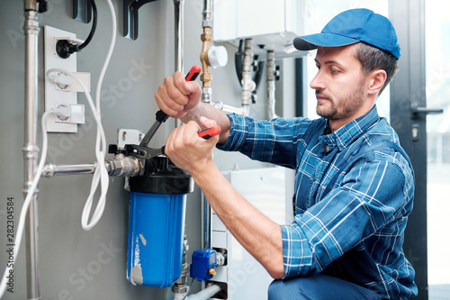 Obraz Young plumber or technician installing or repairing system of water filtration - fototapety do salonu