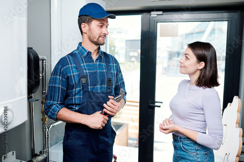 Cuadros en Lienzo  Young casual housewife looking at technician or plumber