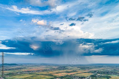 Foto auf AluDibond Akt Beautiful rain cloud and rain over the fields. Aerial photography.
