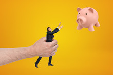 Big Hand Holding Small Businessman Reaching Out With His Both Hands For Cute Pink Piggy Bank Floating In Air On Amber Background.