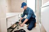 Fototapeta Łazienka - Young plumber or technician preparing detail for bathtub installation