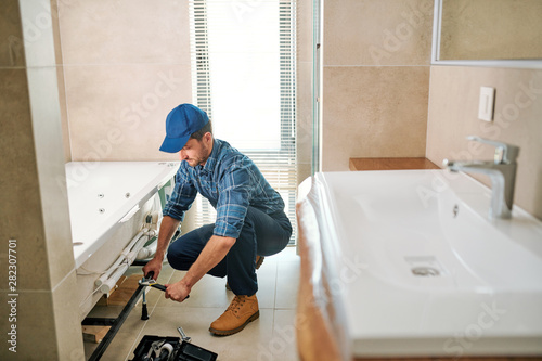 Fotografía  Young worker in uniform sitting on squats while fixing or fastening detail