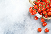 Bunch Of Juicy Organic Red Cherry Tomatoes Arranged W/ Green Basil Leaves In Wicker Basket, Stone Background. Polished Vegetables. Clean Eating Concept. Vegetarian Diet. Copy Space, Flat Lay, Top View