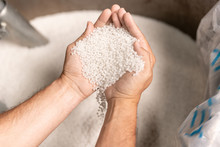 View Of Modern Factory Worker Hands Holding Pile Of White Polymer Pellets