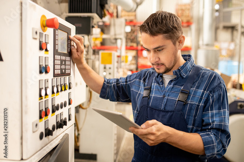 Young factory technician looking through online instructions by control panel