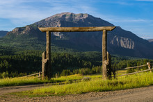 A Rustic Wood Gate Made From Old Weathered Logs In A Typical Western USA Scene Of Fields, Forest And A High Mountain Peak On A Ranch In The Rocky Mountains Near Pagosa Springs, Colorado