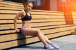 canvas print picture - strrong muscular girl pumping the abdominals while sitting on the wooden bench. full length side view photo.copy space.