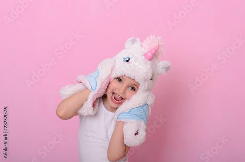 Fototapeta  caucasian beautiful little girl in a hat with  unikorn