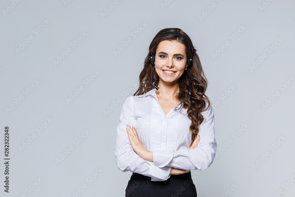 Fototapeta Young friendly operator woman agent with headsets standing near gray background. Call Center Service. Photo of customer support or sales agent in smart casual wear with crossed arms.