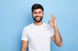 canvas print picture - positive attractive Arab young man showing ring gesture with fingers.close up portrait, good job, agreement concept. I am OK, approval. studio shot.guy being satisfied with suggestion