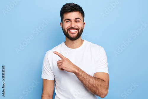 Fotografiet  Young handsome charming man showing something with index finger, place for text, advert, copy space