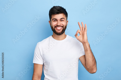 Carta da parati  positive attractive Arab young man showing ring gesture with fingers