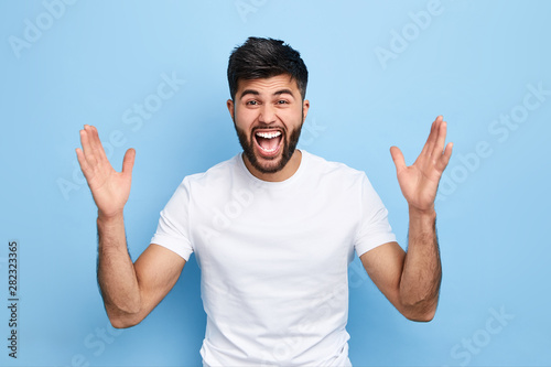 Fotomural  Cheerful handsome happy guy with wide opened mouth raising his hands up, having eyes full of happiness, rejoicing his achievements