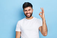 Happy Funny Bearded Man Winking His Eye And Showing Ok Sign, Isolated On Blue Background, Everything Is Under Control. Joke , Fun Concept