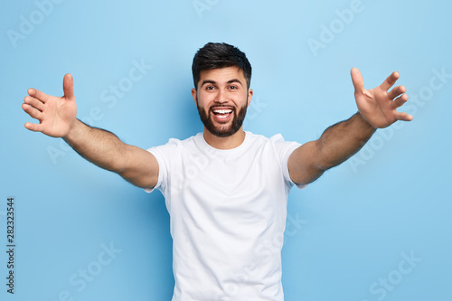 Fotografía  happy handsome Arab bearded young man standing with raised arms, he wants to hug his friend, isolated on blue background