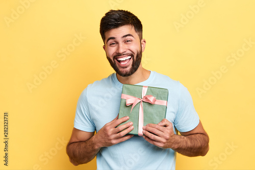 Fotomural  handsome bearded overjoyed man wearing casual clothes holding present box standing isolated over yellow background,Birthday party