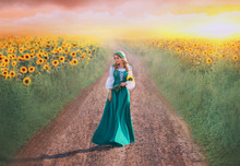Charming Girl In Green Long Dress With White Shirt Walks Along Road, Lady With Blond Braids Holds Yellow Flowers In Hands, Rural Beauty Returns Home From Field, Art Photo With Pink Sky At Sunset