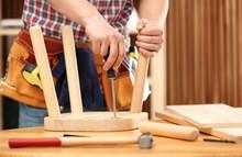 Young Working Man Repairing Wooden Stool Using Screwdriver Indoors, Closeup