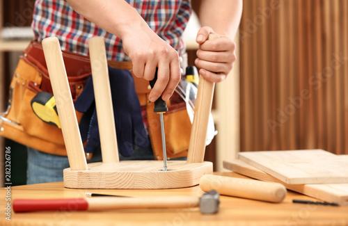 Young working man repairing wooden stool using screwdriver indoors, closeup Wallpaper Mural